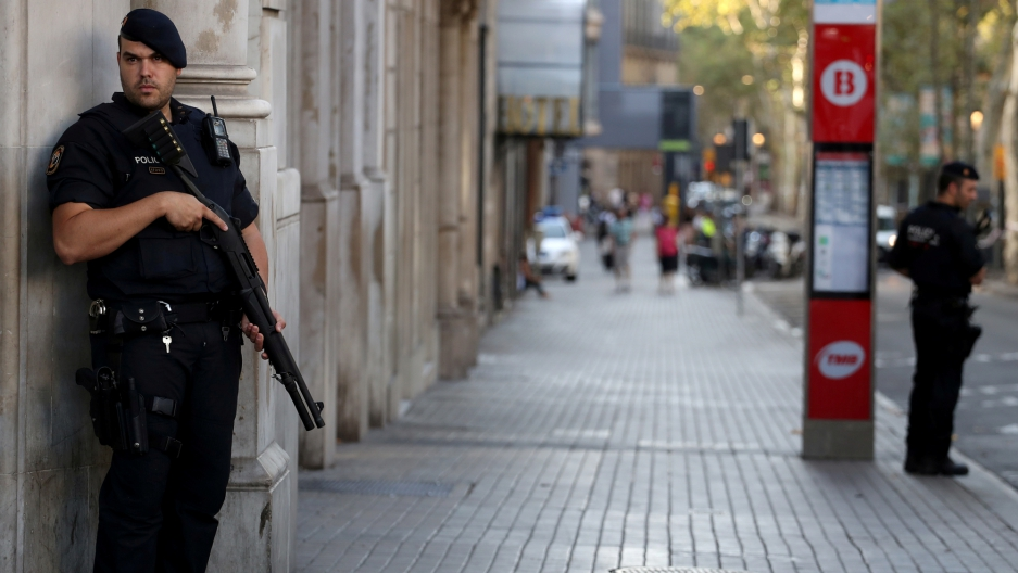 Armed Catalan Mossos d'esquadra officers stand guard at Las Ramblas street where a van crashed into pedestrians in Barcelona.