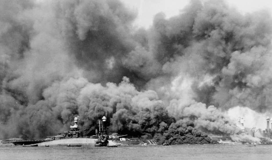 'Battleship Row' after the Japanese attack on Pearl Harbor on 7 December 1941. The capsized USS Oklahoma is visible in the foreground, behind her is USS Maryland, while USS West Virginia burns furiously on the right.
