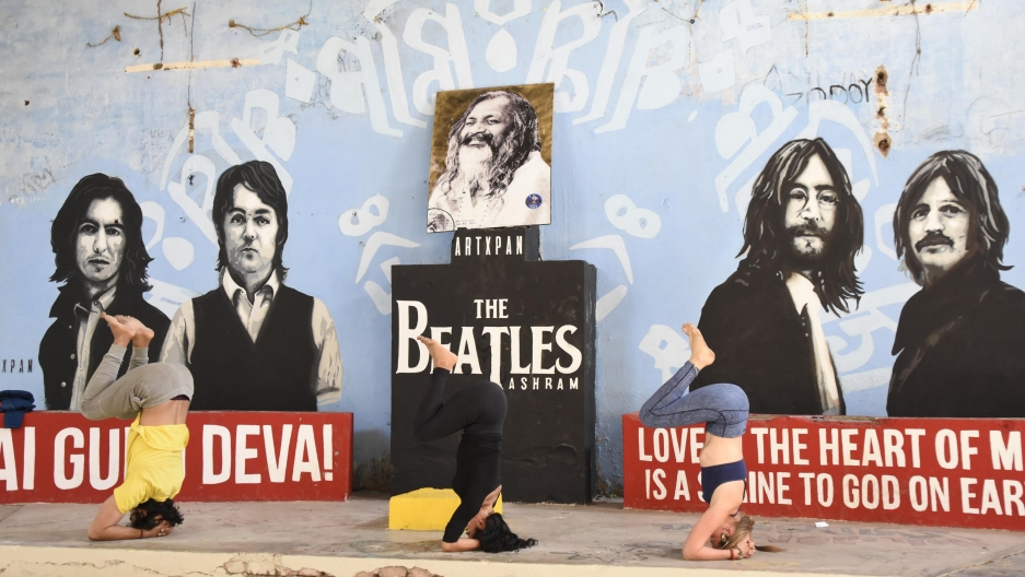 Women practice yoga in front of Beatles-themed displays at the ashram of Maharishi Mahesh Yogi in Rishikesh