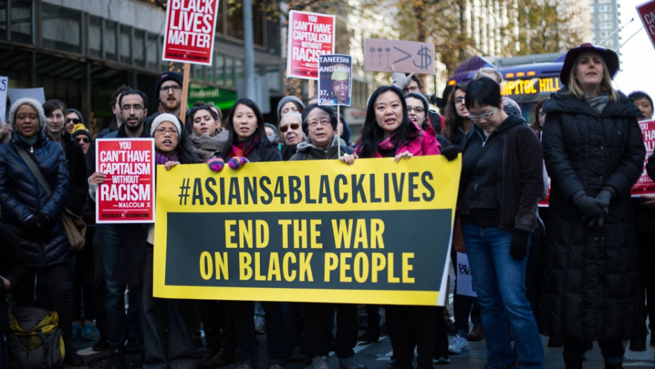 Protesters show solidarity with Black Lives Matter by holding a sign on the street