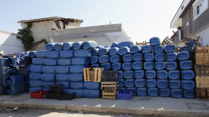 Blue jerry cans, usually used by smugglers ferrying oil from Syria to Turkey, are stacked for sale in front of a shop in the Turkish border town of Hacipasa.