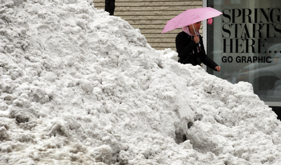 """Spring is coming"" — A pedestrian walks past a pile of snow in Boston."