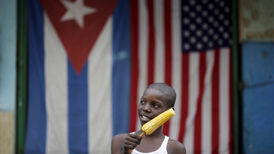 Jimmy Blanco, 9, holds a corncob in front of the Cuban and the U.S. flags in Havana, March 23, 2016. Struggling under a US embargo, many Cubans hope an easing of US-Cuban trade relations will bring material improvements to their lives.