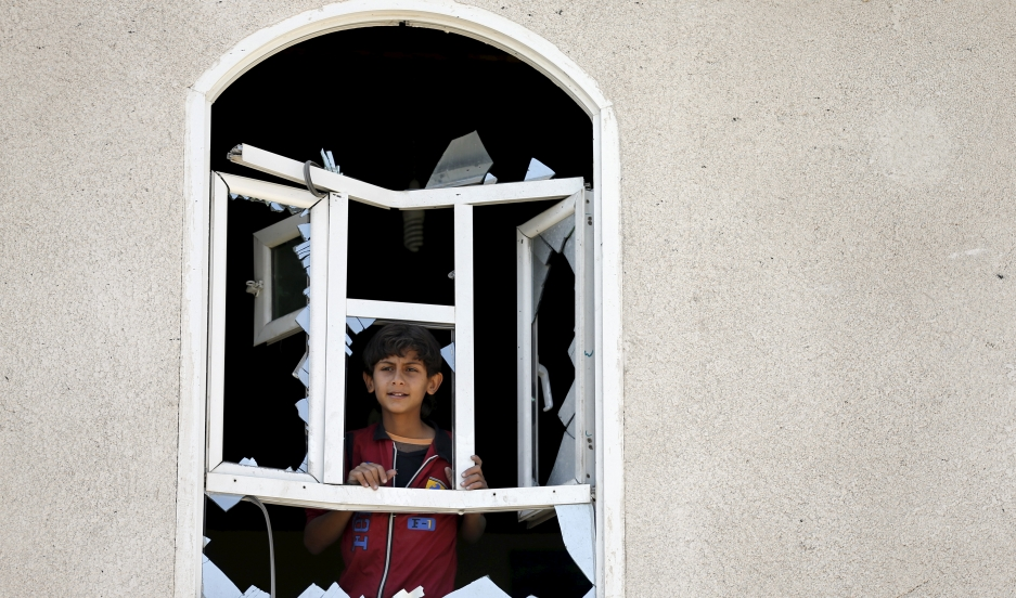 A boy looks through a window of his home damaged by an air strike near Sanaa Airport March 31, 2015.