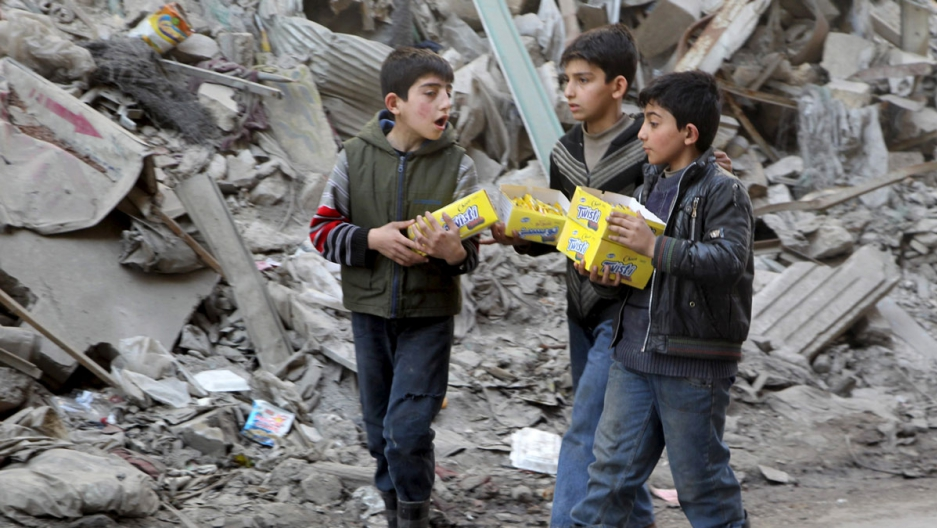 Boys carry boxes of biscuits near rubble of damaged buildings in Aleppo, March 2, 2016.