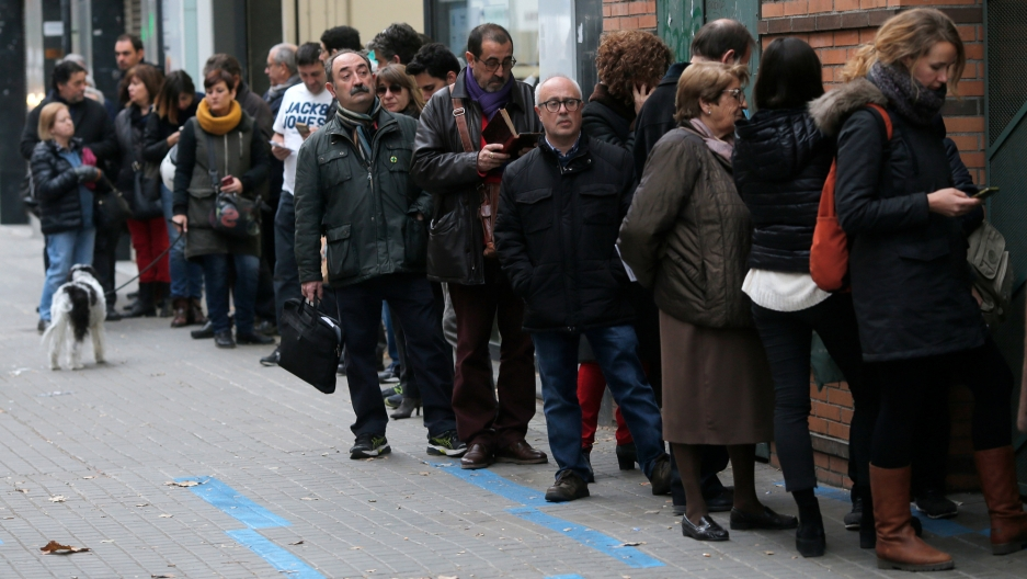 People wait a line as long as three business fronts to vote in Catalonia's regional elections.