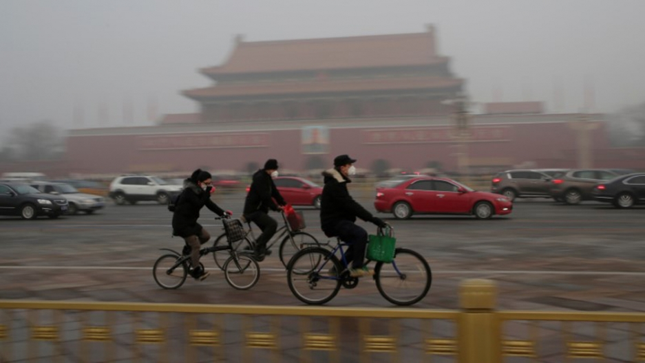 Three bicyclists wearing face masks ride past Tiananmen Gate.
