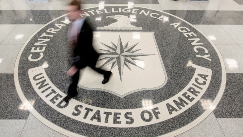 A man in a suit walk over the seal of the CIA at CIA headquarters.