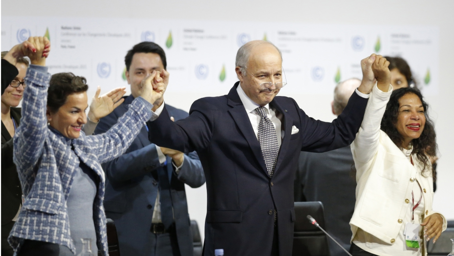 French Foreign Minister Laurent Fabius (C), president-designate of the UN climate summit, and Christiana Figueres (L), executive secretary of the UN Framework Convention on Climate Change, celebrate during the final session of the World Climate Change Con