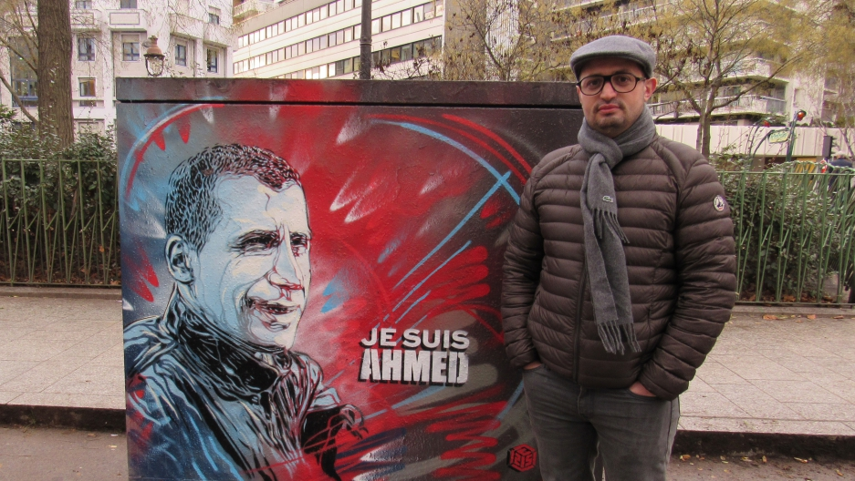 Djamel Adane next to a portrait of Ahmed Merabet, the police officer killed the day of the Charlie Hebdo attacks. Adane was there, and he held Merabet's hand while they waiting for the ambulance to arrive.