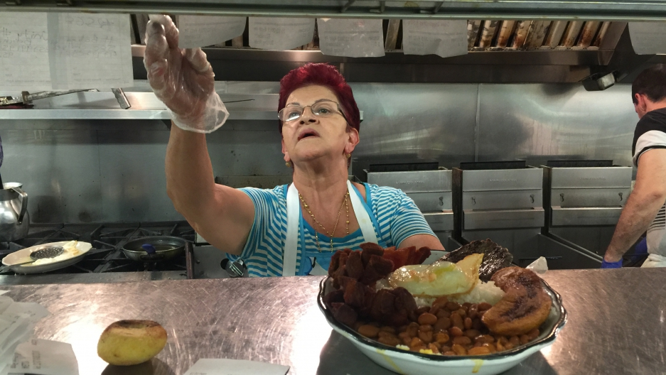 The owner of El Peñol restaurant in East Boston with a bandeja paisa.