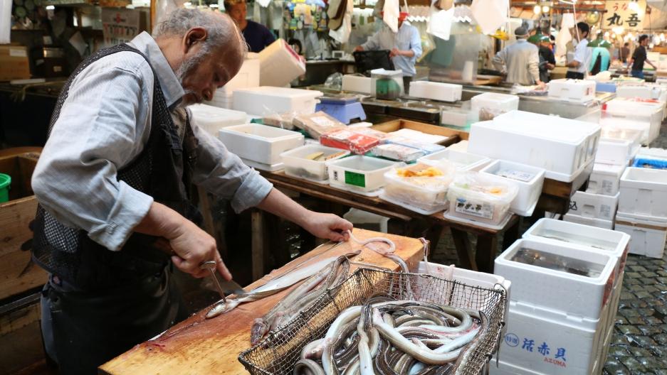 A Tsukiji shopkeeper prepares a basket of live eels for sale.