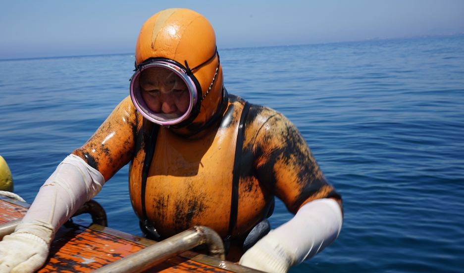 A haeynyo woman climbs aboard the boat. They wear orange diving suits so commercial ships can spot them more easily and steer clear.