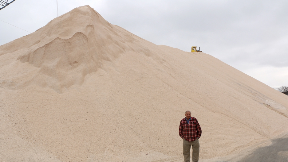 Terminal manager Paul Lamb stands before one of the piles of salt at Eastern Minerals, Inc. in Chelsea, Massachusetts. They bring in hundreds of thousands of pounds of salt every year.
