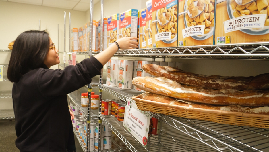 Woman reaching up to top of shelf to get cereal box, shelf has bread and other food products