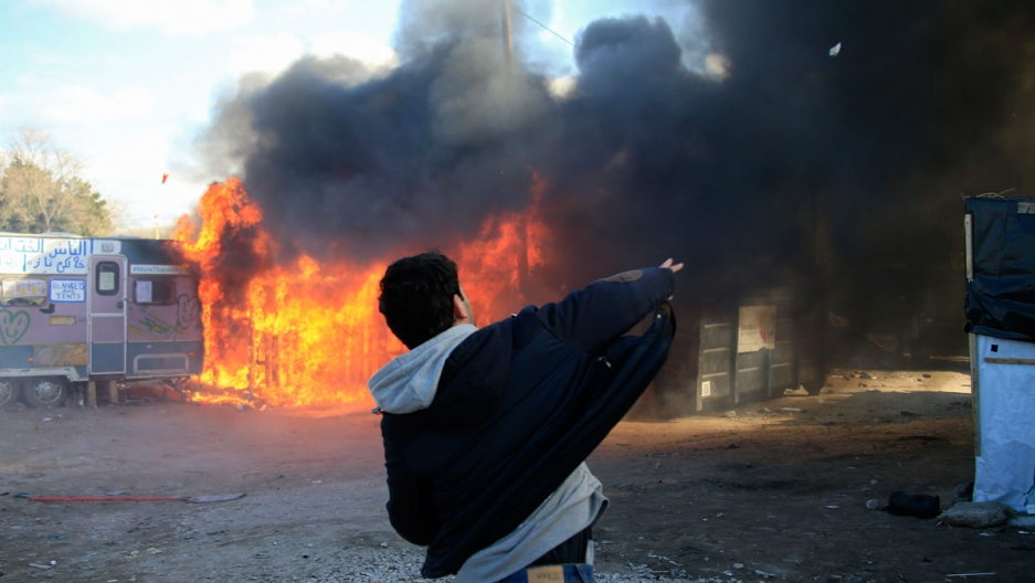 """A youth throws a stone as smoke and flames rise from a burning makeshift shelter in protest against the partial dismantlement of the camp for migrants called the """"jungle,"""" in Calais."""