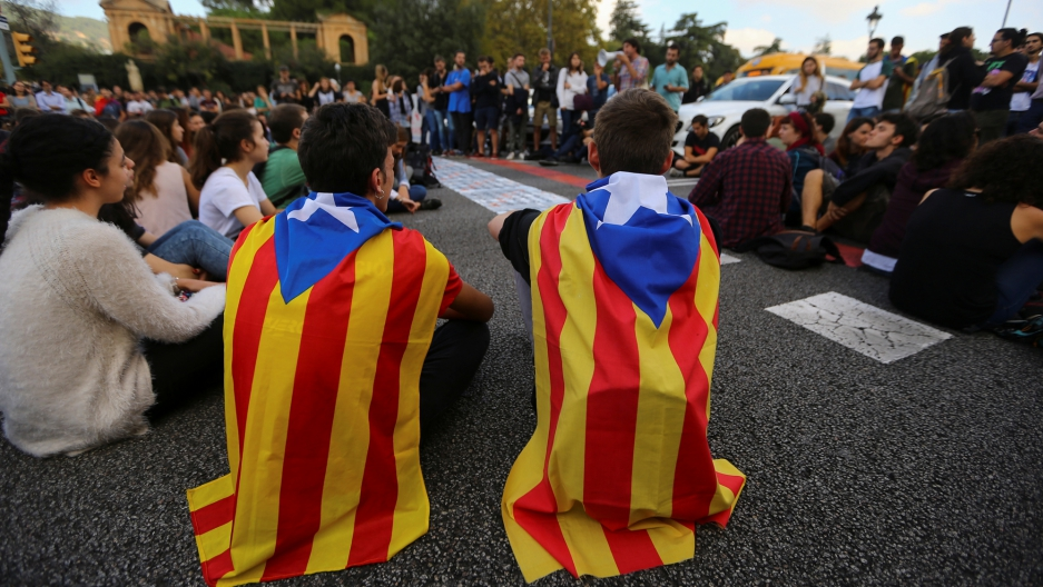 Students wear Catalan flags as they block a street during a protest in Barcelona.