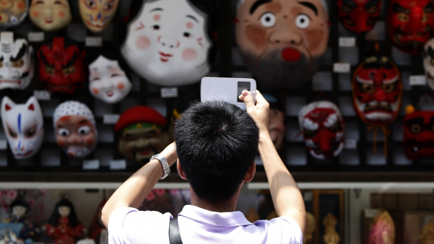 A tourist from China takes pictures of Japanese traditional masks at a souvenir shop in Asakusa district in Tokyo.