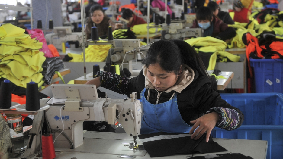 An employee works at a garment factory, which exports products overseas, in Hefei, Anhui province January 19, 2015.