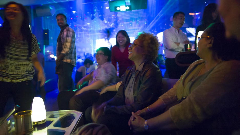 Woman seated in club with people walking around her