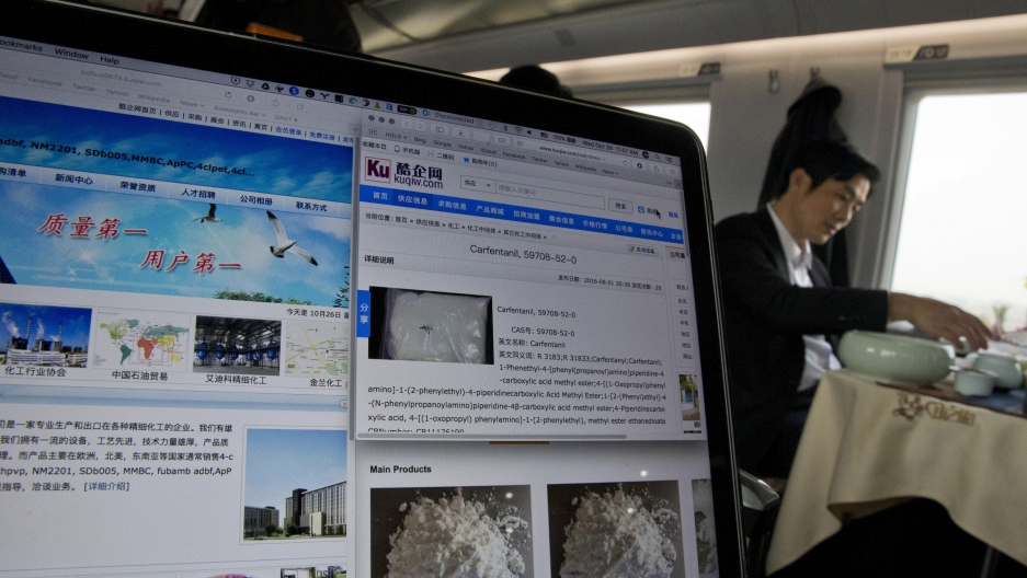 A man drinks tea near a computer screen displaying websites of companies selling the lethal synthetic opioid carfentanil online on a train leaving Beijing on Wednesday, Oct. 26, 2016. Use of the deadly chemical carfentanil by drug dealers has exploded acr
