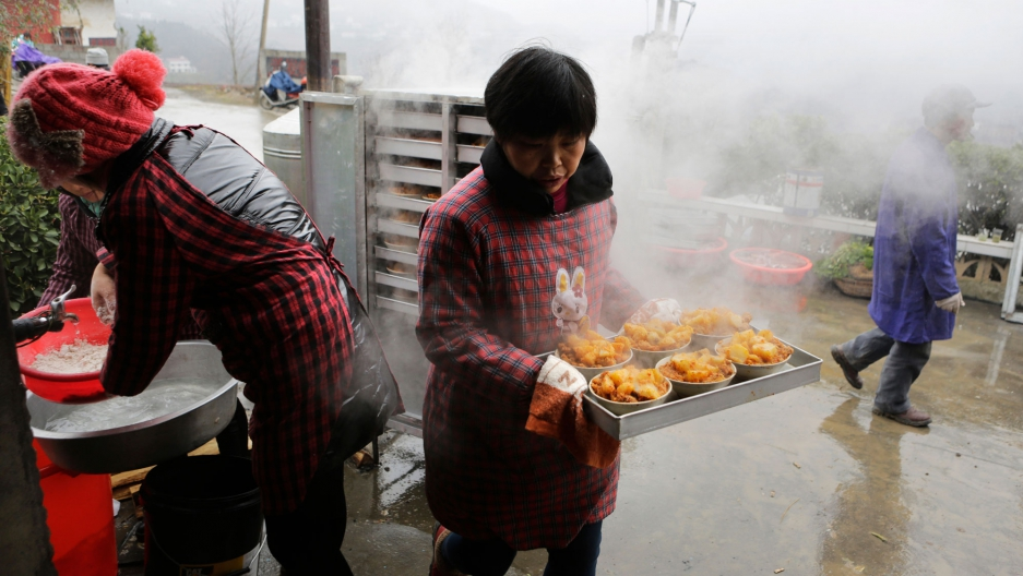 A local cook prepares a traditional ethnic Tujia wedding feast during celebrations marking the Lunar New Year in China's Hubei province.