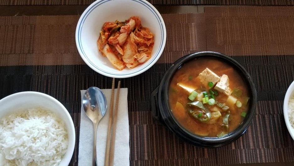 Dishes of rice, stew and kimchi on a wooden table