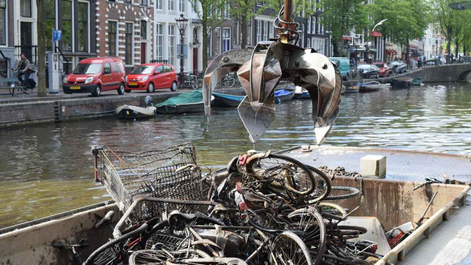 Bike fishermen use a giant claw to remove bikes and other detritus from the Amsterdam canals. The bikes are deposited on a trash barge, and later recycled for scrap.