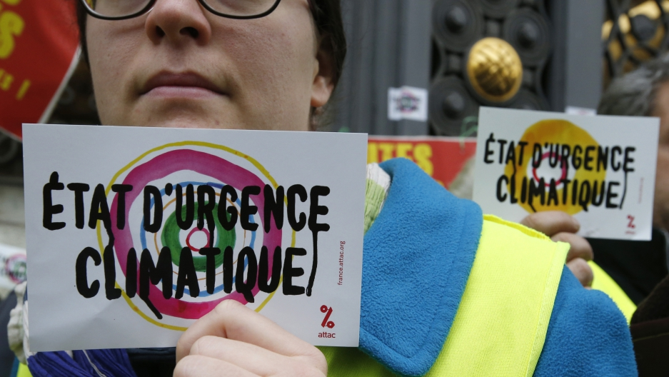 "Environmental activists hold placards reading ""Climatic emergency state"" during a demonstration as part of the World Climate Change Conference 2015 (COP21) in Paris."