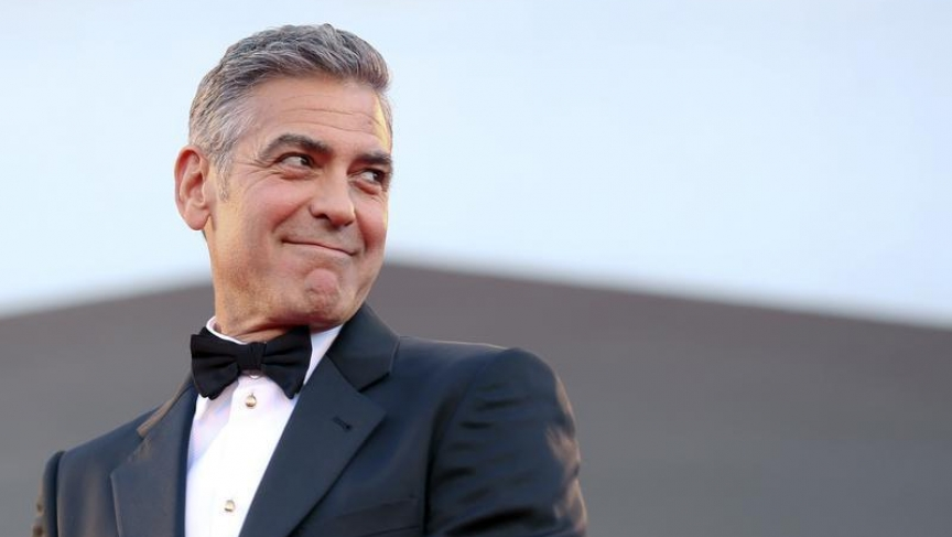 """U.S. actor George Clooney smiles as he arrives on the red carpet for the premiere of """"Gravity"""" at the 70th Venice Film Festival in Venice August 28, 2013. Clooney and Sandra Bullock star in Alfonso Cuaron movie """"Gravity"""" which debuts at the festival."""
