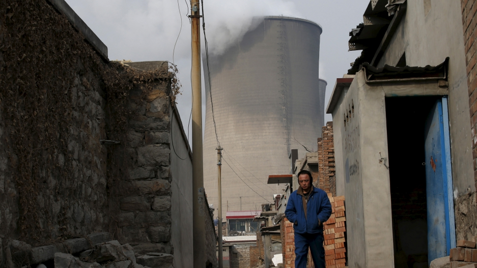 A man makes his way in a village located next to chimneys of coal-fired power plant in Shijiazhuang, Hebei province, China. On December 2nd, Beijing announced it would reduce its annual carbon dioxide emissions from coal-fired power generation by 180 mill