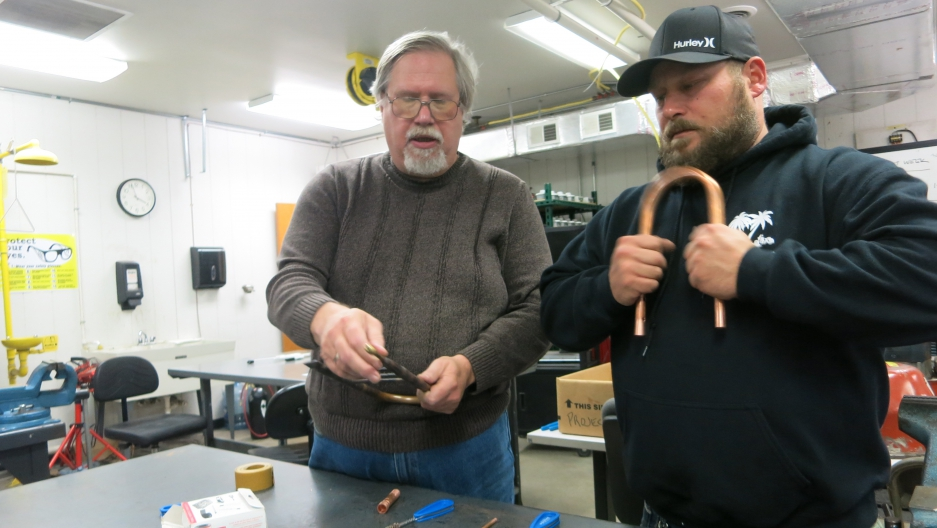 HVAC Instructor Dennis Matney (left) teaches Travis Keppen how to repair pipes in a classroom in Burns Harbor, Indiana.