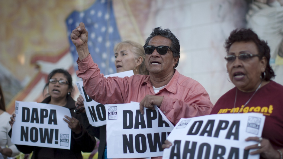 """One man and three women hold signs that say """"DAPA now!"""" and """"DAPA Ahora!"""" before a wall covered with a mural, barely visible."""