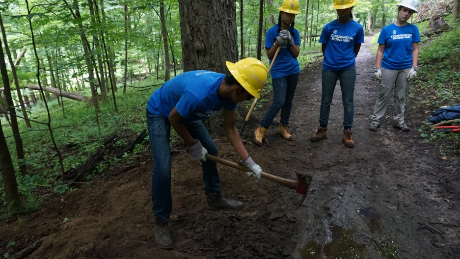 Several young people wearing gloves and helmets work in a park, one digs with a shovel