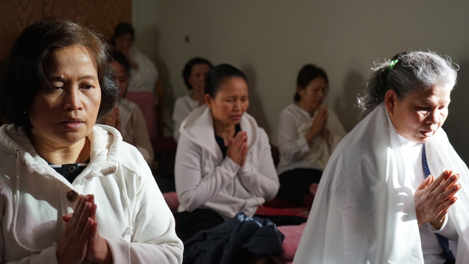 Cambodian women meditating in the Metta Center's meditation lounge, sitting cross-legged with palms pressed together