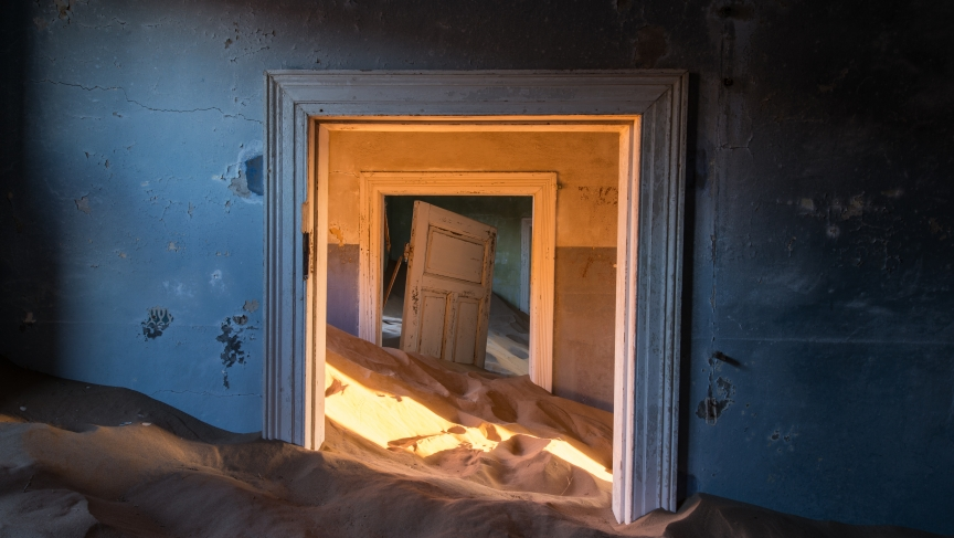 A doorway half-buried by sand in Kolmanskop, Namibia