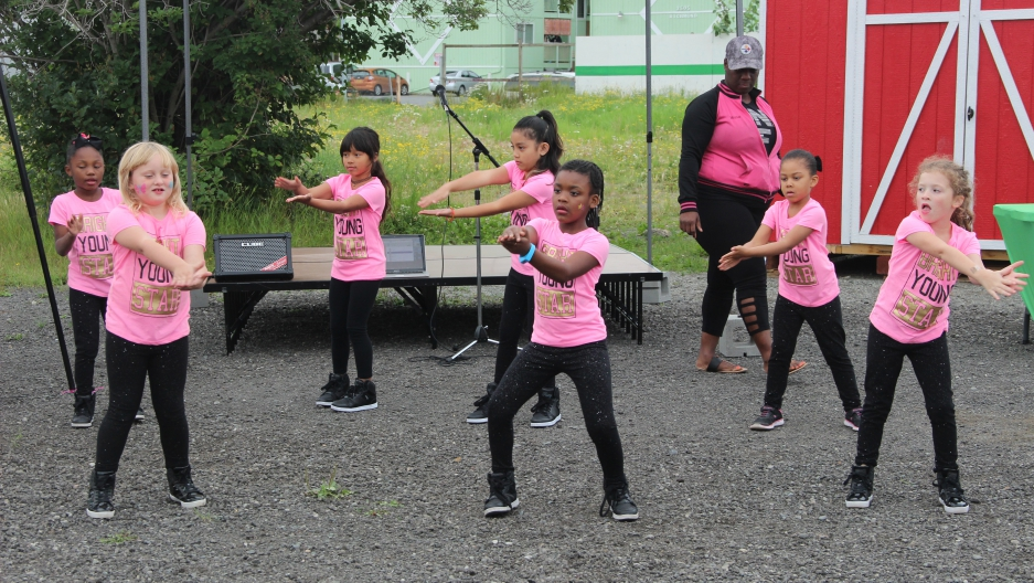 "Girls with the ""Rhythm of Light"" dance troupe perform at a weekly farmer's market in Anchorage's Mountain View neighborhood."