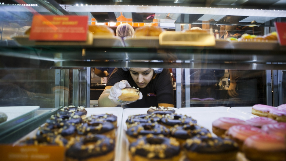 An employee takes a donut from a display cabinet at the Dunkin' Donuts store in New Delhi, India.