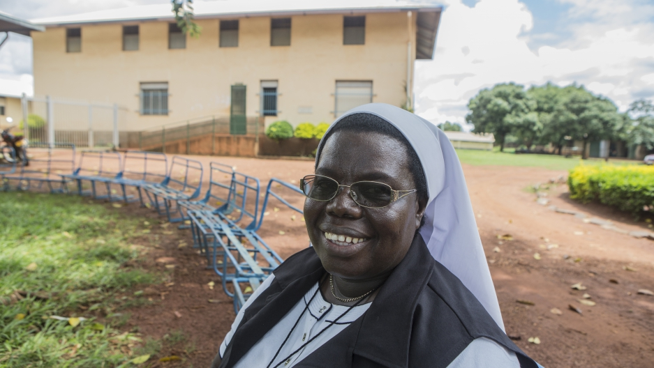 Sister Rosemary Nyirumbe sitting on a bench in front of St. Monica's Vocational School in Gulu, Uganda.