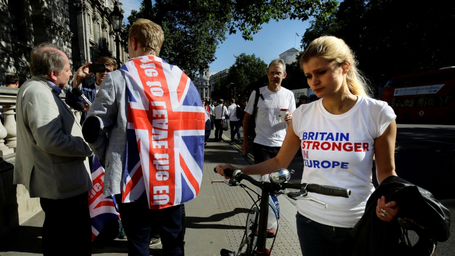 A vote remain supporter walks past a vote leave supporter outside Downing Street in London after Britain voted to leave the European Union.