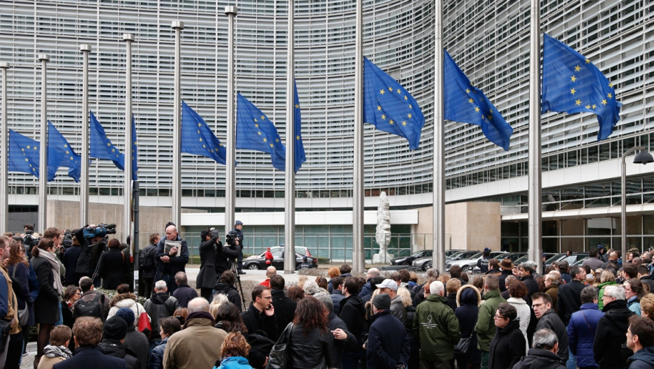 People observe a minute of silence outside the EU Commission Headquarters in Brussels following Tuesday's bomb attacks.