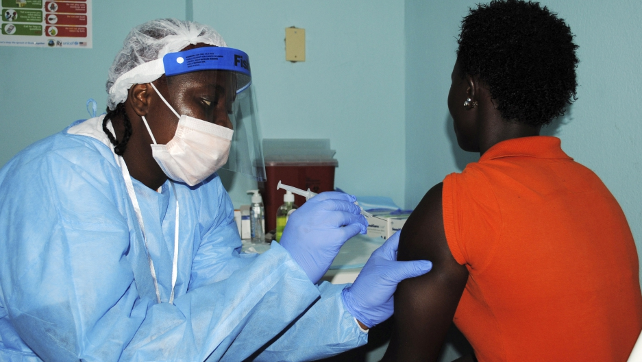 A health worker injects a woman with an Ebola vaccine during a trial in Liberia