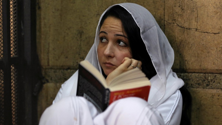 Aya Hijazi, founder of a nonprofit charity that looks after Egyptian street children, sat reading a book inside a holding cell as she faced trial in a courthouse in Cairo, Egypt on March 23.