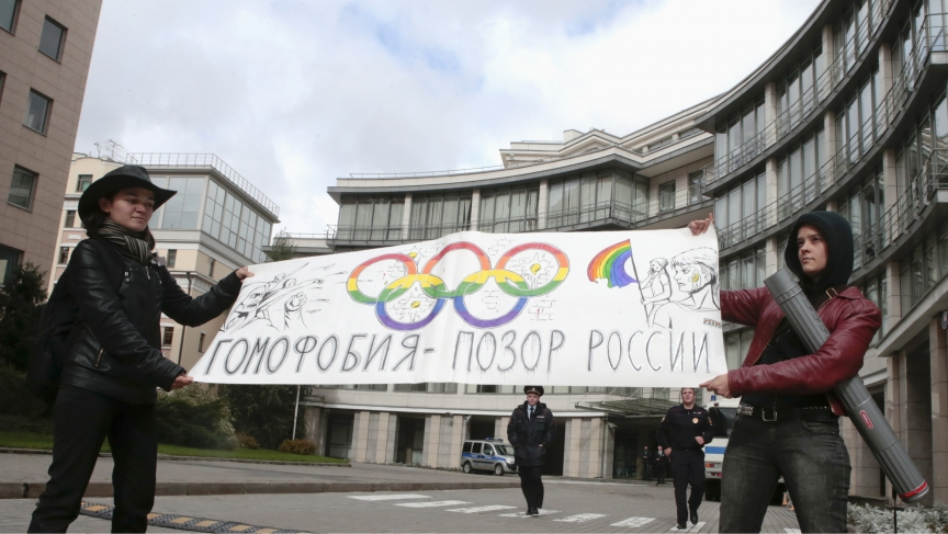 """Gay rights activists in Moscow held a banner that reads """"Homophobia is the shame of Russia,"""" as they protested in front of the Sochi 2014 organizing committee building in Moscow on September 25, 2013."""