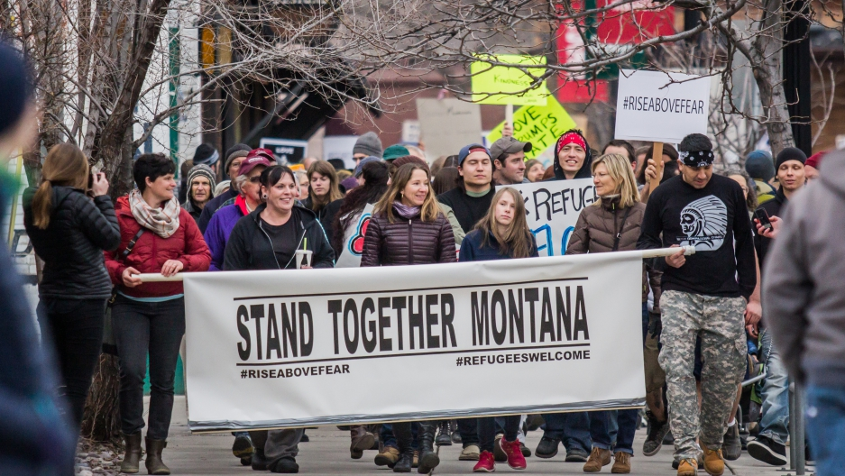 A group of activists march down a street with a large banner that reads, STAND TOGETHER MONTANA.