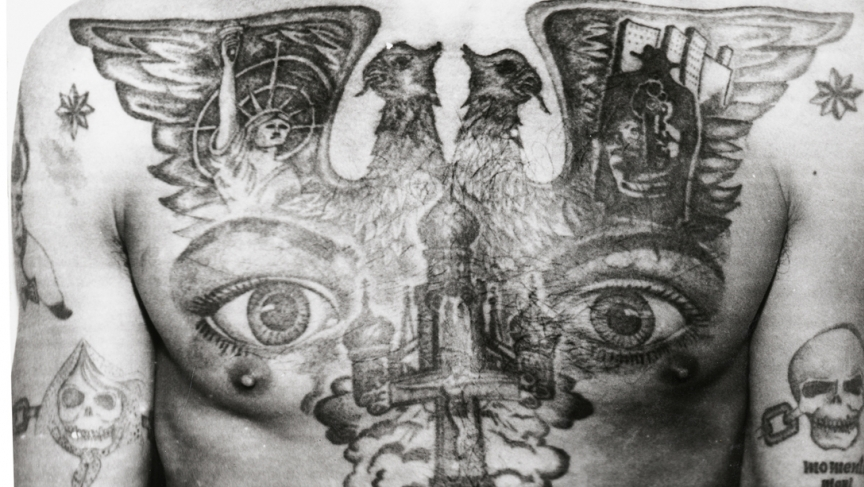"""The eyes tattooed on this Soviet prisoner's chest signify """"I can see everything"""" and """"I am watching,"""" the powerful tattoo of a criminal """"overseer."""" The eight-pointed stars tattooed on the shoulders mark the bearer as an """"authoritative'"""" thief."""