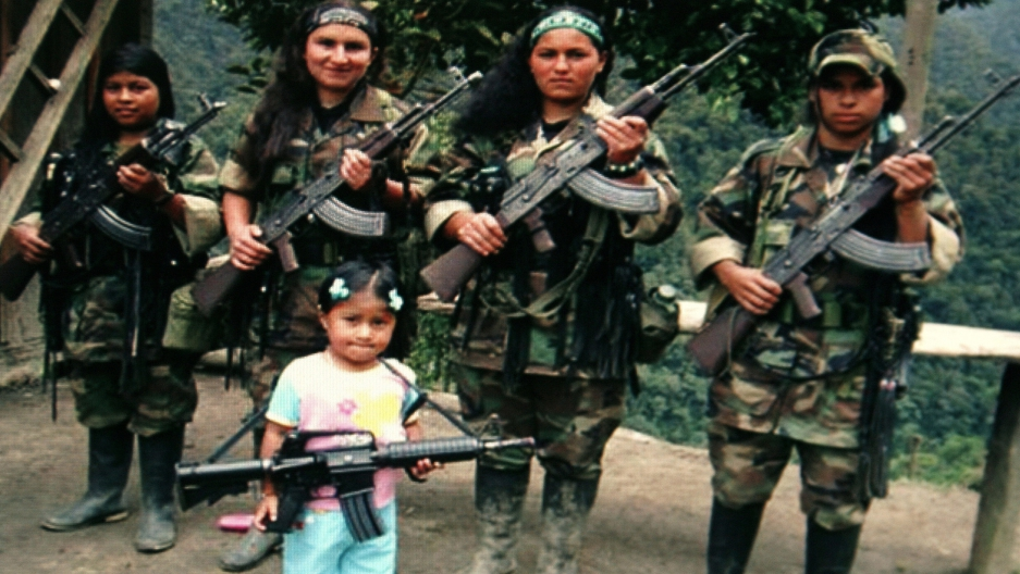 FARC rebels pose with an unidentified girl holding a weapon in southern Colombia in this undated photo confiscated by the Colombian police and released to the media on November 12, 2009. Police said that the photo was found on the body of a rebel FARC kil
