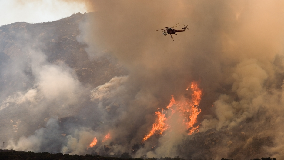 Helicopter dropping water on wildfire