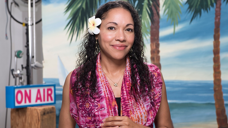 """Woman in front of tropical set, """"On Air"""" sign, with flower in her hair"""
