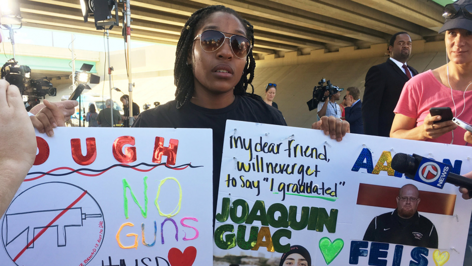 Tyra Hemans, a 19-year-old senior at Marjory Stoneman Douglas High School, sobs as she holds signs honoring slain teachers and friends near the police cordon around the school in Parkland, Florida, Feb. 15, 2018.